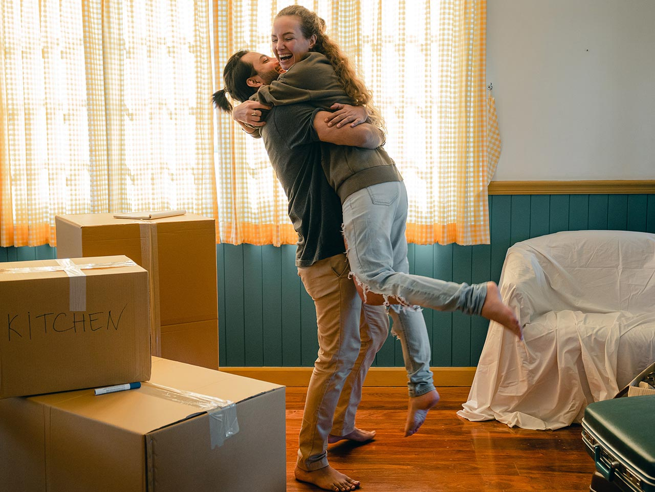 happy couple just moved in to buy to let surrounded by boxes