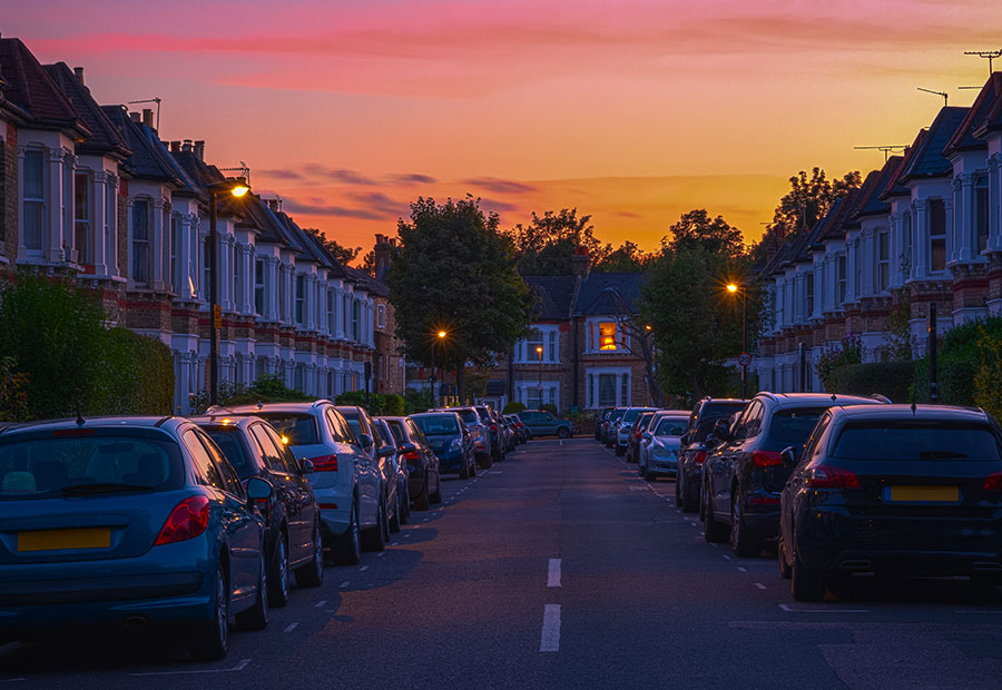 typical english street with houses and cars ate sunset