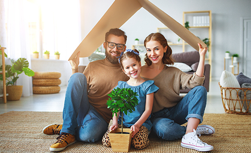 family of three sitting smiling under a model roof